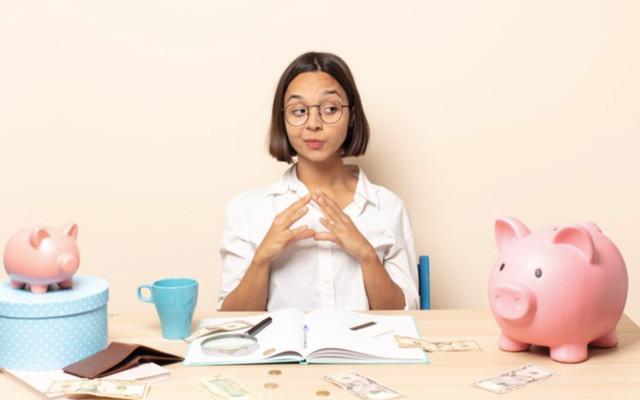 Девушка за столом занимается составлением личного финансового плана