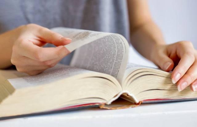 Девушка листает и читает очень толстую книгу