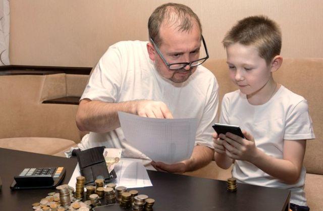 Отце с сыном изучают семейный бюджет и доходы семьи