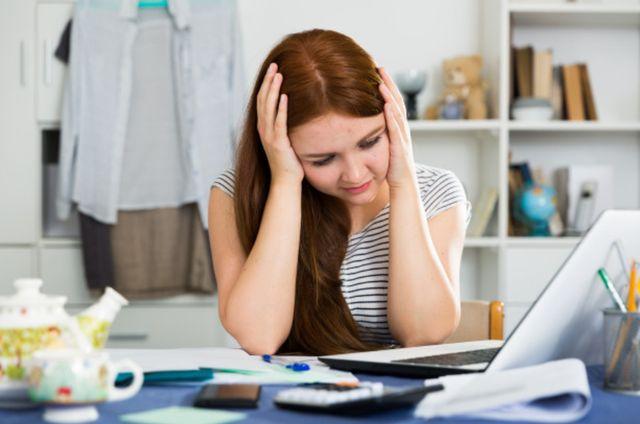 Молодая женщина сидит за столом и изучает свои финансовые документы