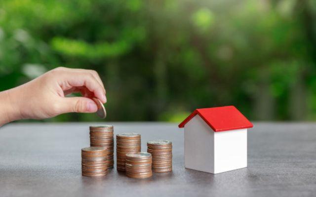 Рука добавляет монетку к накоплениям на дом