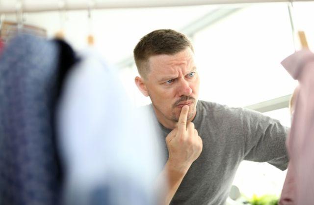 Задумчивый мужчина рассматривает одежду на вешалке
