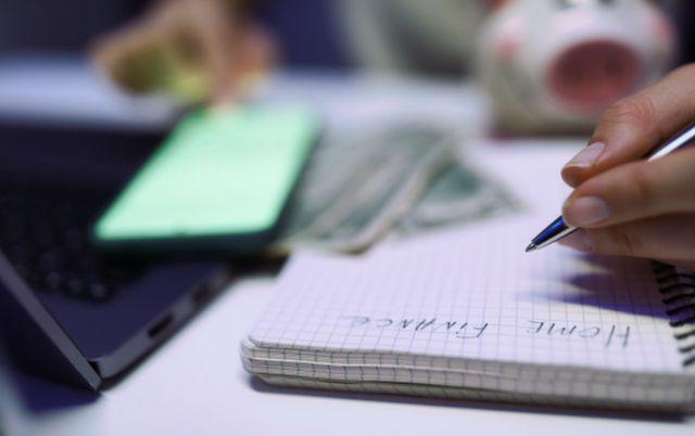 Женские руки вписывают в блокнот бюджет личных финансов
