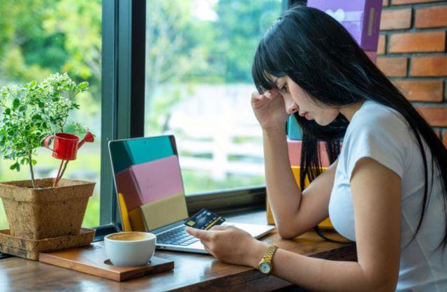 Темноволосая девушка страдает из-за проблем с долгами по кредитной карте