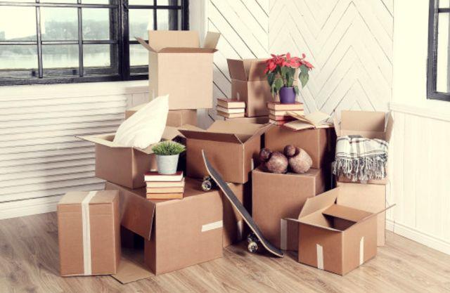 Много вещей в коробках в углу комнаты