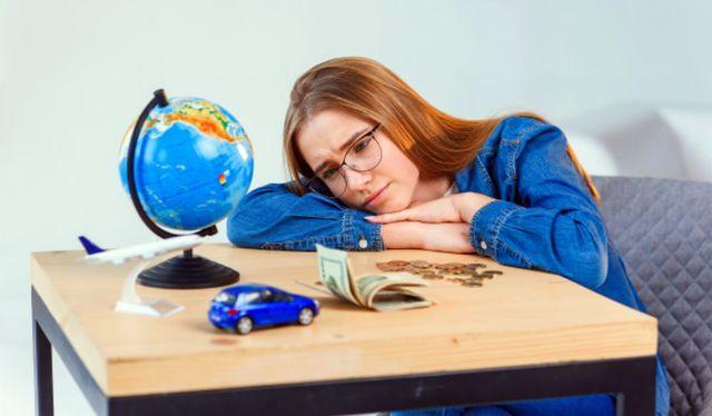 Грустная девушка смотрит на деньги и мечтает о будущих покупках