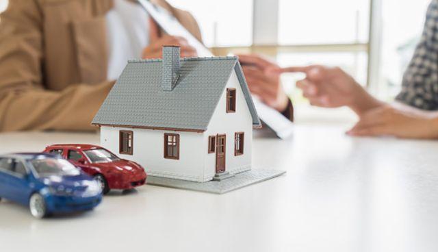 Модель дома и автомобилей на фоне людей оформляющих страховку