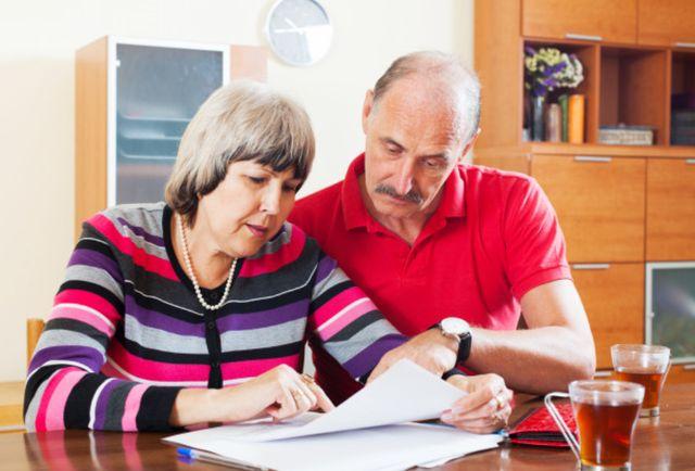 Семейная пара изучает счета за ежемесячные услуги