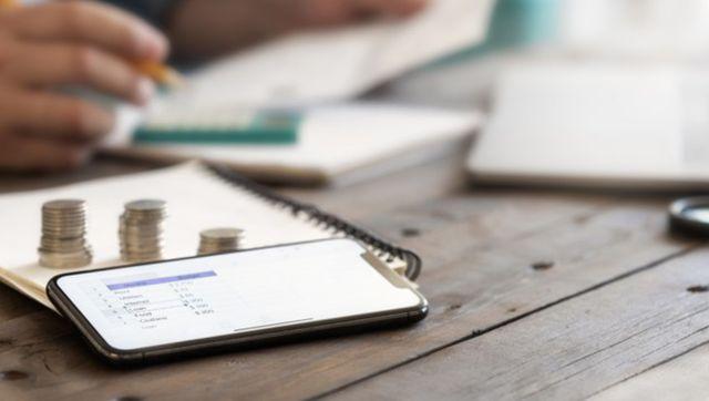 Мужчина планирует домашние расходы с помощью журнала и смартфона