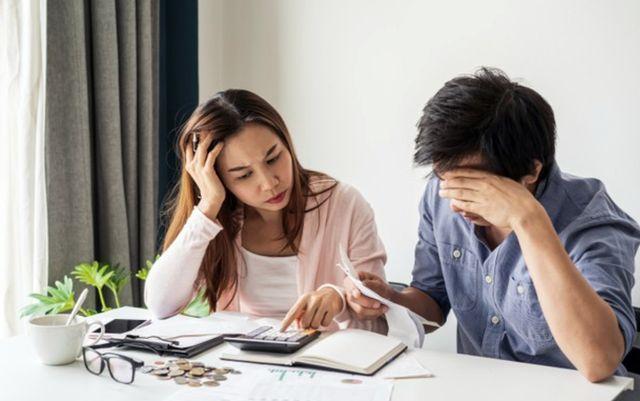 Молодая семейная пара сидит за столом и составляет список расходов