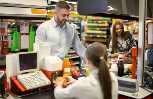 Молодой мужчина и девушка закупают продукты питания на кассе супермаркета
