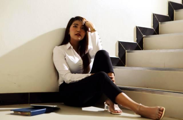 Унылая девушка сидит на полу возле лестницы и думает о финансовых проблемах