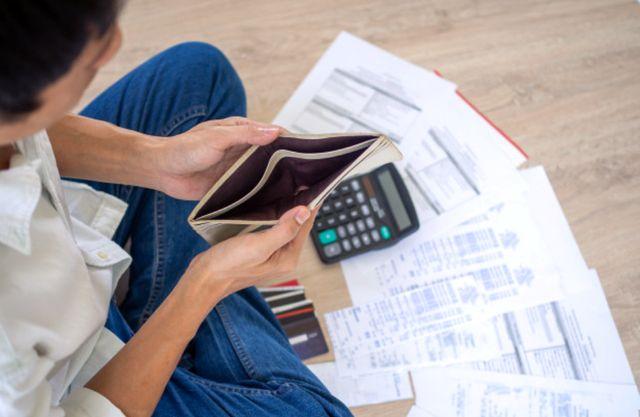 Молодой человек изучает счета и заглядывает в пустой кошелёк