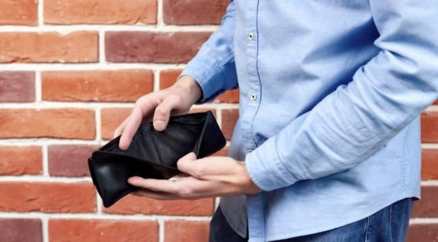 Мужчина заглядывает в пустой кошелёк