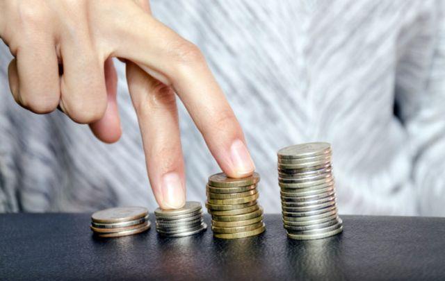 Мужчина шагает пальцами по стопкам монет