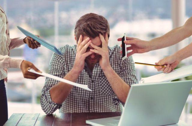 Мужчина в окружении коллег протягивающих инструменты для работы