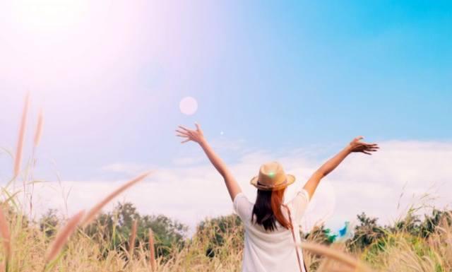 Женщина в шляпе радуется ясному небу с поднятыми руками
