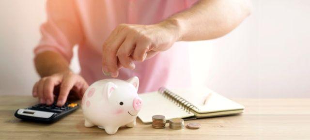 Рука мужчины кладёт монету в копилку для будущих инвестиций