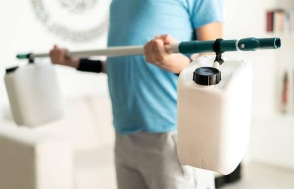 Мужчина тренируется в домашних условиях с помощью подручных средств