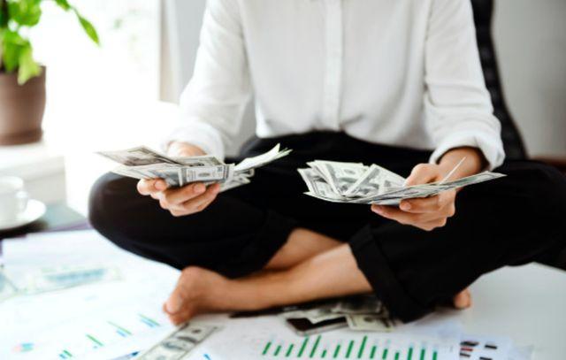 Девушка сидит, подогнув ноги, и держит в руках долларовые купюры