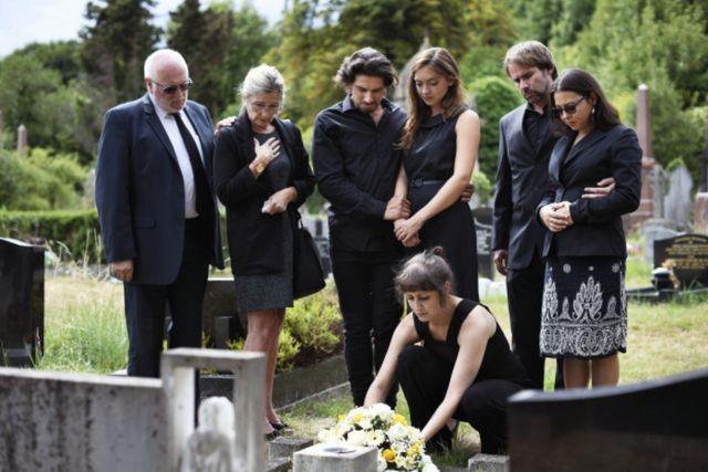 Семья возлагает цветы на могилу