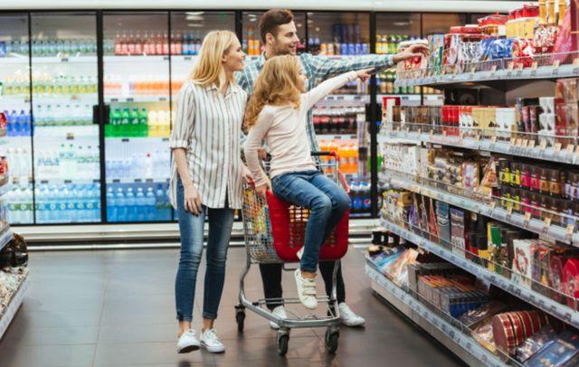 Семейная пара с дочкой выбирает товары в магазине