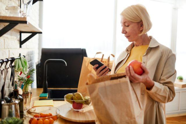 Женщина проверяет продукты питания купленные в магазине
