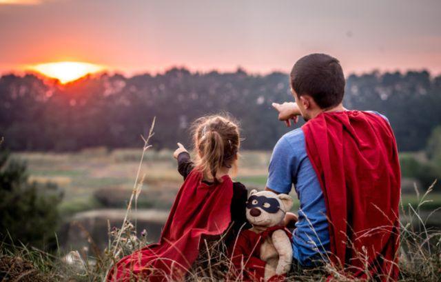 Девочка с папой в костюмах супергероев смотрят на закат солнца