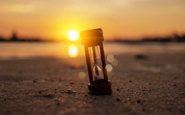 Песочные часы на фоне заходящего солнца