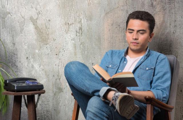 Молодой человек сидит на стуле у стены и читате книгу