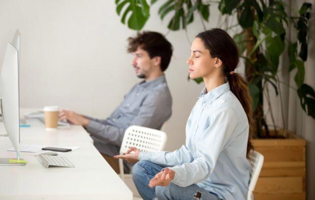 Девушка медитирует во время перерыва от работы