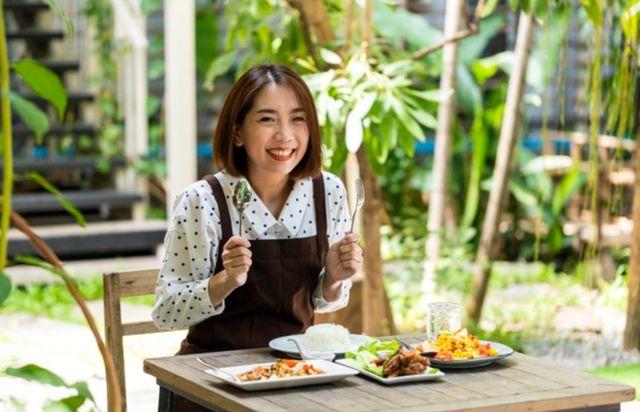 Милая азиатская девушка с улыбкой готовится позавтракать за уличным столом