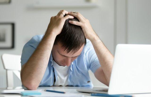Мужчина возле ноутбука обхватил голову руками