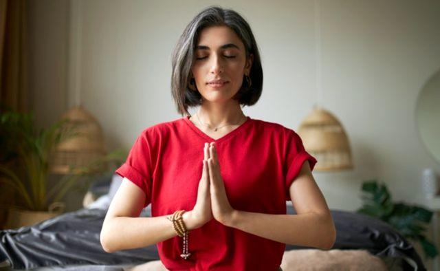 Привлекательная молодая женщина с преждевременным поседением волос медитирует дома с закрытыми глазами