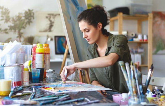 Серьёзная девушка с темными волосами занимается художественным рисованием