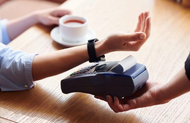 Женская рука с умными часами оплачивает чашку кофе бесконтактным способом