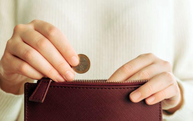 Руки девушки кладут монету в кошелёк