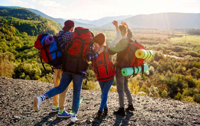 Вид со спины четырёх друзей в туристическом походе