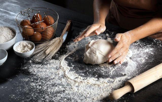 Мужчина замешивает тесто на кухонном столе