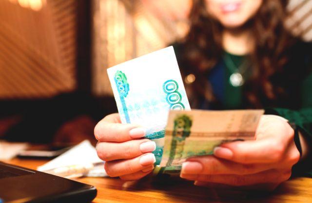 Девушка отсчитывает купюры по 1 тысяче рублей