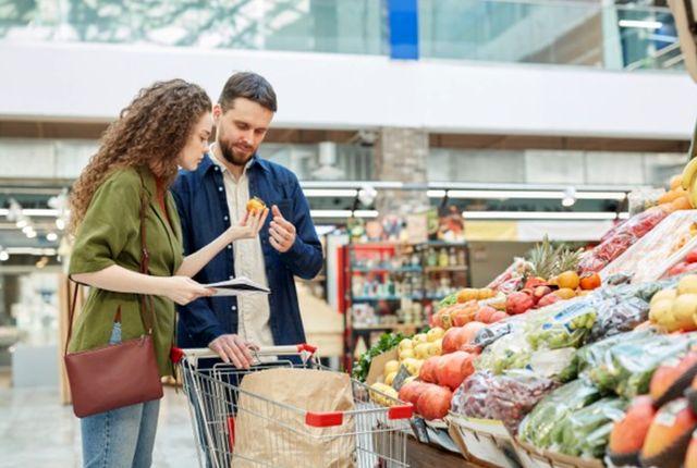 Молодая семейная пара тщательно выбирает продукты в магазине