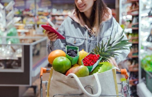 Девушка со смартфоном в руках катит продуктовую тележку по магазину