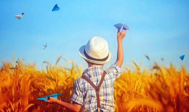 Ребёнок запускает бумажные самолётики над пшеничным полем