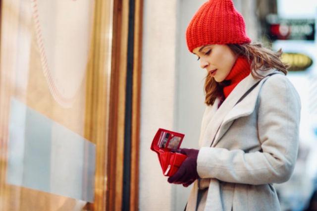 Девушка смотрит в пустой кошелёк после покупок