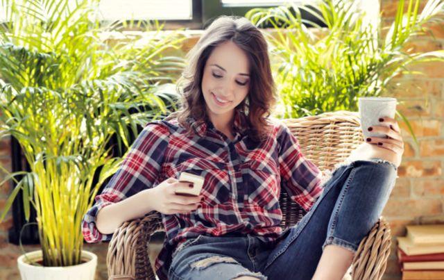 Девушка сидит в плетённом кресле с чашкой и смартфоном в руках