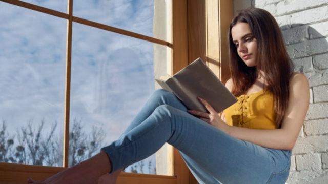 Девушка сидит на подоконнике и читает книгу