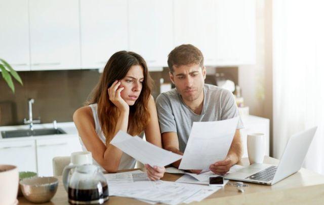Молодая семейная пара изучает счета за коммунальные услуги