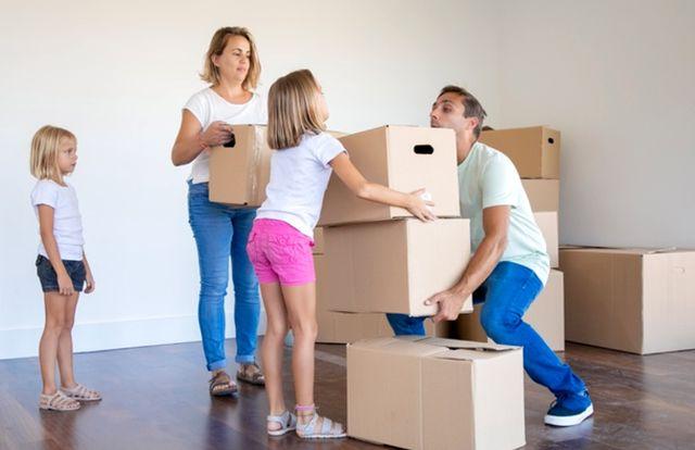 Молодая семья с детьми заносит коробки в новый дом