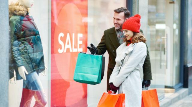 Счастливая пара закупает одежду на распродажах