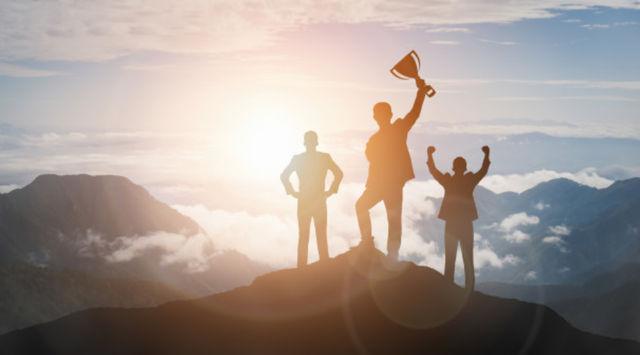 Силуэты победителей на вершине горы